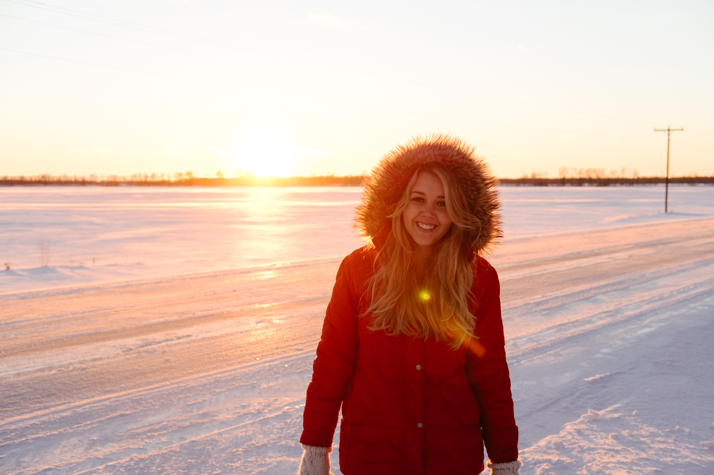 Debora Dahl wearing a red coat in the snow with the sunset behind her