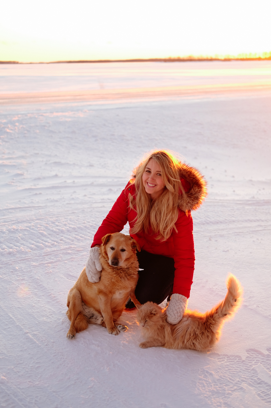 Debora Dahl wearing a red coat in the snow with the sunset behind her with a dog and a cat