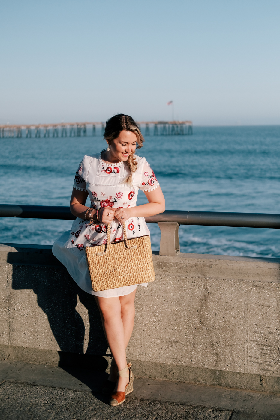 Debora Dahl, bolsa de palha e vestido branco bordado